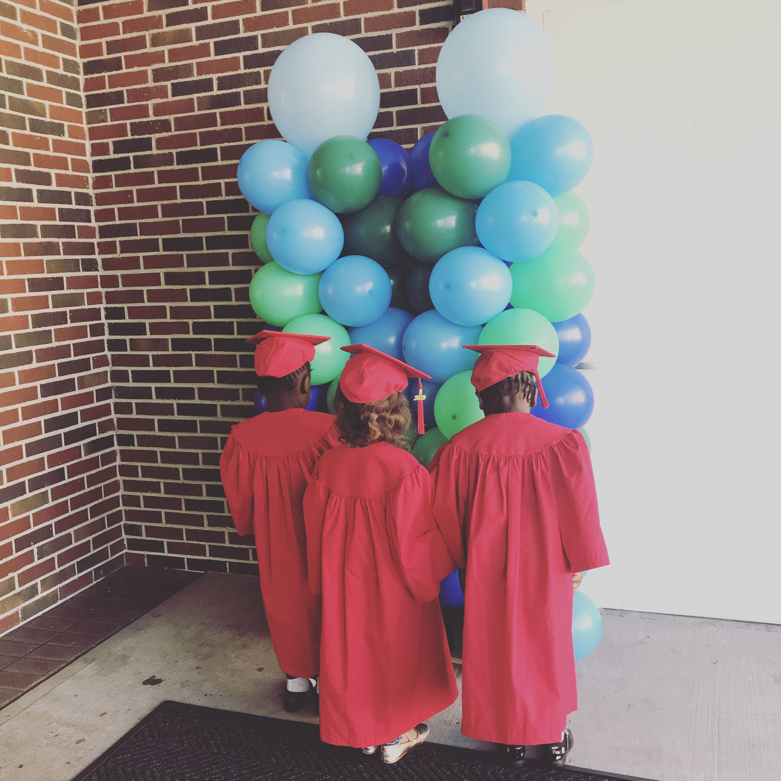 3 preschoolers in red cap and gowns